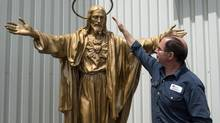 Auto body shop owner Gilles Perron looks at the restored statue of the Sacred Heart, June 11, 2014 in Lac-Megantic, Que. The statue will be replaced on its base in time for the first year anniversary celebrations. (Paul Chiasson/The Canadian Press)