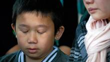 Ten-year-old Eric Ut, son of deceased Langley mushroom farm worker Ut Van Tran, cries as his mother, Hong Dang, speaks to reporters at an inquest into the 2008 deaths and injuries on the farm, in Burnaby, B.C., on May 10, 2012. (Darryl Dyck for The Globe and Mail/Darryl Dyck for The Globe and Mail)