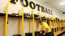 Player Brad Morton packs his bag in the dressing room after a press conference by the football players of the University of Waterloo Warriors football team. (DAVE CHIDLEY/The Canadian Press)