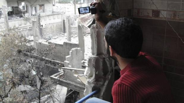 An activist takes photos of damaged buildings after what opponents of the regime said was shelling by forces loyal to Syria's President Bashar al-Assad in Homs on Oct. 22, 2012. (Muhammad Al-Ibrahim/Shaam News Network/REUTERS)