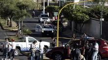 Investigators and members of a forensic team gather around a car where the new tourism minister of Jalisco state, Jose de Jesus Gallegos, was shot dead on March 9, 2013. (REUTERS)