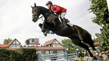 Olympic gold medalist Eric Lamaze of Canada jumps a water jump on his horse Hickstead at the Spruce Meadows Nations' Cup team jumping event in Calgary, Sept. 6, 2008. (Todd Korol/Reuters/Todd Korol/Reuters)