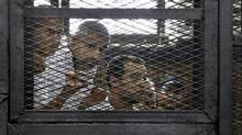From left, Australian correspondent Peter Greste, Canadian-Egyptian acting bureau chief of Al-Jazeera Mohamed Fahmy, and Egyptian producer Baher Mohammed, appear in a defendant's cage in a courtroom in Cairo, Egypt, Monday, June 23, 2014. (Heba Elkholy/AP)