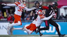 The B.C. Lions' Mike Edem, centre, grabs at the Calgary Stampeders' Marquay McDaniel, right, as Chandler Fenner, far left, looks on during the Western Division final on Nov. 20, 2016. (Todd Korol/The Canadian Press)