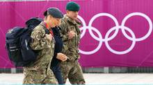 Members of the armed forces walk past the perimeter of the Olympic Park in Stratford, east London, July 15. The government had to deploy additional troops after it became clear security firm G4S was unlikely to fulfill its contract for 10,400 guards. (Andrew Winning/REUTERS)
