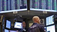 Traders work at the Knight Capital kiosk on the floor of the New York Stock Exchange. (BRENDAN MCDERMID/REUTERS)
