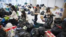 Volunteers organize about 11,000 kilograms of items collected for Syrian refugees in Vancouver, B.C., on Dec. 3. (Rafal Gerszak For The Globe and Mail)