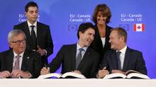 Canadian Prime Minister Justin Trudeau, center front, sits with European Commission President Jean-Claude Juncker, left, and European Council President Donald Tusk, right, as they sign the Comprehensive Economic and Trade Agreement (CETA) during an EU-Canada summit at the European Council building in Brussels, Sunday, Oct. 30, 2016. (Francois Lenoir/The Associated Press)