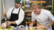 Chef Gordon Ramsay, right, speaks to reporters during a cooking demonstration at his new restaurant 'Laurier Gordon Ramsay', in Montreal, Tuesday, August 9, 2011 as head chef Guillermo Russo looks on. (Graham Hughes / CP)