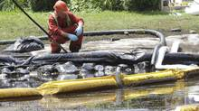 In this July 29, 2010, file photo, a worker watches water come out of a pipe in Talmadge Creek where booms have been set up to contain an oil spill in Marshall Township, Mich., near the Kalamazoo River. (Paul Sancya/PAUL SANCYA/AP)