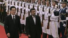 Chinese President Hu Jintao (L) and his Iranian counterpart Mahmoud Ahmadinejad review an honour guard during a welcoming ceremony at the Great Hall of the People in Beijing June 8, 2012. Mr. Ahmadinejad is in China to attend the Shanghai Co-operation Organization (SCO) summit. (Jason Lee/Reuters)
