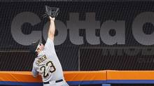 Pittsburgh Pirates right fielder Travis Snider  climbs the fence to rob New York Mets' Mike Baxter of a home run during the second inning of a their baseball game at Citi Field in New York, Thursday, Sept. 27, 2012 (Kathy Willens/Associated Press)