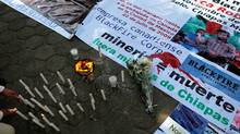 A demonstrator lights candles next to a banner with a picture of anti-mine activist Mariano Abarca Robledo during a protest outside the Canadian embassy in Mexico City, on Dec. 3, 2009. (Eduardo Verdugo/Eduardo Verdugo/AP)