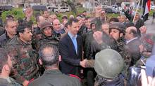 Syrian President Bashar al-Assad shakes hands with soldiers at the Baba Amr neighbourhood of Homs on Tuesday. (Sana/Reuters)