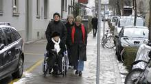 "Lee Carter, red scarf, and her husband Hollis Johnson walk with her 89-year-old mother Kathleen ""Kay"" Carter, who suffered from spinal stenosis, in Switzerland . Her family took her there in January 2010 to end her life."