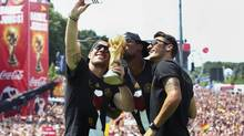 Germany's Lukas Podolski, Jerome Boateng and Mesut Oezil pose for a 'selfie' with the World Cup trophy during celebrations to mark the team's World Cup victory (POOL/Reuters)