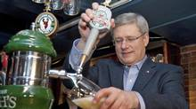 Prime Minister Stephen Harper pours pints of beer during a campaign stop at a Halifax tavern on March 31, 2011. (Adrian Wyld/THE CANADIAN PRESS)