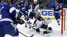 Winnipeg Jets goalie Al Montoya prepares to make a save on a shot by Tampa Bay Lightning's Vincent Lecavalier as Lightning's Ryan Malone (12) and Jets' Zach Bogosian (44) look on during the second period of their NHL game in Tampa, Florida, March 7, 2013. (MIKE CARLSON/REUTERS)