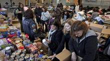 Teachers and volunteers organize donations before school starts at P.S. 38 on the Staten Island borough of New York Monday. Many schools in the New York area reopened after closure from Hurricane Sandy last week. (MICHAEL KIRBY SMITH/NYT)