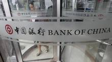 A woman leaves a branch of Bank of China in Beijing in this file photo. (JASON LEE/REUTERS)