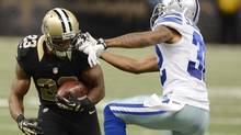 New Orleans Saints running back Pierre Thomas gets face masked by Dallas Cowboys cornerback Orlando Scandrick (© USA Today Sports / Reuters)