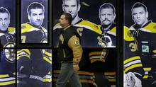 A man wearing a Boston Bruins jacket walks by a photo display of Bruins hockey players outside a pro shop at TD Garden Monday, Jan. 7, 2013. (Associated Press)