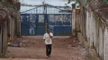 A man in Conakry, capital of Guinea, walks on July 30, 2014, past the entrance to the property – seen at left, where a man is sitting – where a stampede took place the night before during a rap concert. (YOUSSOUF BAH/ASSOCIATED PRESS)