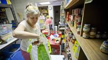 Bonnie Parsons, a volunteer with the Weston Food Bank, fills a grocery bag with foodstuffs, June 28, 2011. (Tim Fraser for The Globe and Mail/Tim Fraser for The Globe and Mail)