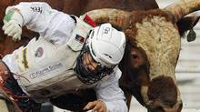 Devon Mezei gets hit in the back by the bull Bad Rumour during the rodeo at the Calgary Stampede in Calgary, Alberta, July 10, 2010. REUTERS/Todd Korol (TODD KOROL)