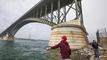 Kyle Horning, left, and Gordon Carlson fishing under the Peace Bridge on the American side in Buffalo, N.Y., May 9, 2013. New York Gov. Andrew Cuomo's handling of differences over the international bridge is giving the wider world a glimpse of how he often wields power. (BRENDAN BANNON/NYT)