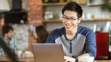 Happy cheerful young asian male in glasses smiling and using laptop in cafe (Vadym Drobot)