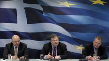Greece's Finance Minister Evangelos Venizelos, centre, addresses reporters during a news conference in Athens after the country reached a second bailout agreement as economic adviser George Zanias, left, and deputy finance minister Pantelis Economou keep notes. (YIORGOS KARAHALIS/YIORGOS KARAHALIS/REUTERS)