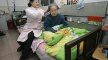 A woman tidies the hair of 106-year-old Liang Guangru at a nursing home in Beijing. The government says China will face a crisis in caring for its elderly unless it can shore up its and social security funds before an explosion in its rapidly aging population. (JASON LEE/REUTERS)