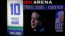 Retired Vancouver Canucks forward Pavel Bure, of Russia, is seen on a video screen as he watches his number 10 retired and lifted to the rafters during a ceremony before the Canucks game against the Toronto Maple Leafs in Vancouver, B.C., on Saturday November 2, 2013. (DARRYL DYCK/THE CANADIAN PRESS)
