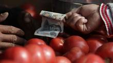China's former chairman Mao Zedong's portrait is seen on a ten yuan banknote as a customer pays for her tomato at a market in Beijing, October 14, 2011. (STRINGER/CHINA/REUTERS)