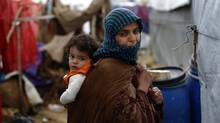 A Syrian refugee carries her baby on her back as she walks at a refugee camp in the town of Hosh Hareem in Lebanon, Jan. 4, 2016. (Hassan Ammar/AP)
