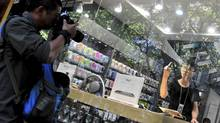 An employee in a fake Apple Store gestures with his middle finger to a photographer trying to take pictures of the store in Kunming, Yunnan province July 21, 2011. (CHINA DAILY/REUTERS/China Daily)