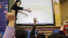Monica Fong from David Livingstone Elementary works on a SMART board in class in Vancouver, BC. The touch-sensitive display connects computer, digital projector and students to show computer image and work. (Lyle Stafford/For the Globe and Mail)