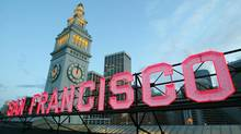A restored neon sign glows from the Ferry Building at dusk in San Francisco, Calif. (ERIC RISBERG/AP)