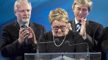 PQ leader Pauline Marois is applauded during a pause in her speech by her husband Claude Blanchet, right, and Jean-Francois Lisee at the party's election headquarters Monday, April 7, 2014 in Montreal. (Paul Chiasson/THE CANADIAN PRESS)