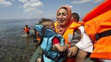 Syrian migrant mother holding her child breaks into tears as they reach the shore in the port town of Mytilini in Greece after crossing the Aegean from Turkey, Aug. 23, 2015. (Visar Kryeziu/AP)