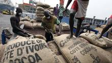 Workers gather bags of cocoa at the port of Abidjan, Ivory Coast. Last week Ghana, the second-largest producer behind Ivory Coast, set its cocoa price at around 25 per cent, or 180 CFA francs (35 cents) higher per kilogram, than the Ivory Coast price of 725 CFA. Ghana's Finance Minister acknowledged that the price difference was likely to lead to smuggling, a topic that both governments had previously been reluctant to broach in public. (LUC GNAGO/REUTERS)