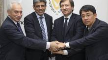 Cyprus's Finance Minister Vassos Shiarly, left, and Energy Minister Neoclis Sylikiotis (centre right) pose for a photograph after the signing of the production and sharing contracts with representatives of Italy's ENI and South Korea's Kogas in Nicosia Jan. 24, 2013. Cyprus licensed the Italian-South Korean consortium to explore three offshore areas lying south and southeast of the island. (ANDREAS MANOLIS/REUTERS)