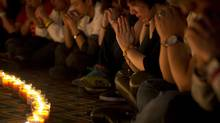 Relatives of Chinese passengers onboard Malaysia Airlines Flight 370 pray during a candlelight vigil for their loved ones at a hotel in Beijing, China, Tuesday, April 8, 2014. (Andy Wong/AP)