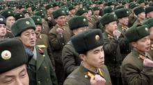 North Korean soldiers clench their fists during a rally celebrating the country's third nuclear test in Pyongyang, in this picture taken and released by Kyodo on Feb.14, 2013. (KYODO/REUTERS)