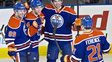 Edmonton Oilers Sam Gagner (89), Taylor Hall (4), Justin Schultz (19) and Andrew Ference (21) celebrate a goal against the Tampa Bay Lightning during third period NHL action in Edmonton, Alta., on Sunday January 5, 2014. (JASON FRANSON/THE CANADIAN PRESS)