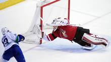 Arizona Coyotes goalie Louis Domingue (35) makes a diving save on Vancouver Canucks center Henrik Sedin (33) during the first period at Gila River Arena in Glendale, AZ on Wednesday, Feb. 10, 2016 (Matt Kartozian/USA Today Sports)