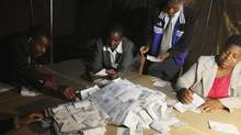 Zimbabwean election officials count ballot papers after the close of voting on a referendum in Harare, on March 16, 2013. Zimbabweans voted on Saturday in the referendum expected to endorse a new constitution that would trim presidential powers and pave the way for an election to decide whether Robert Mugabe extends his three-decade rule. (PHILIMON BULAWAYO/REUTERS)