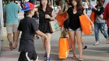 In this Wednesday, Feb. 3, 2016, file photo, tourists from Taiwan carry shopping bags as they walk along Lincoln Road Mall, a pedestrian area featuring retail shops and restaurants in Miami Beach, Fla. (Lynne Sladky/AP Photo)
