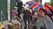 A woman views floral tributes to Drummer Lee Rigby, of the British Army's 2nd Battalion The Royal Regiment of Fusiliers, at the scene of his killing in Woolwich, southeast London May 24, 2013. (PAUL HACKETT/Reuters)